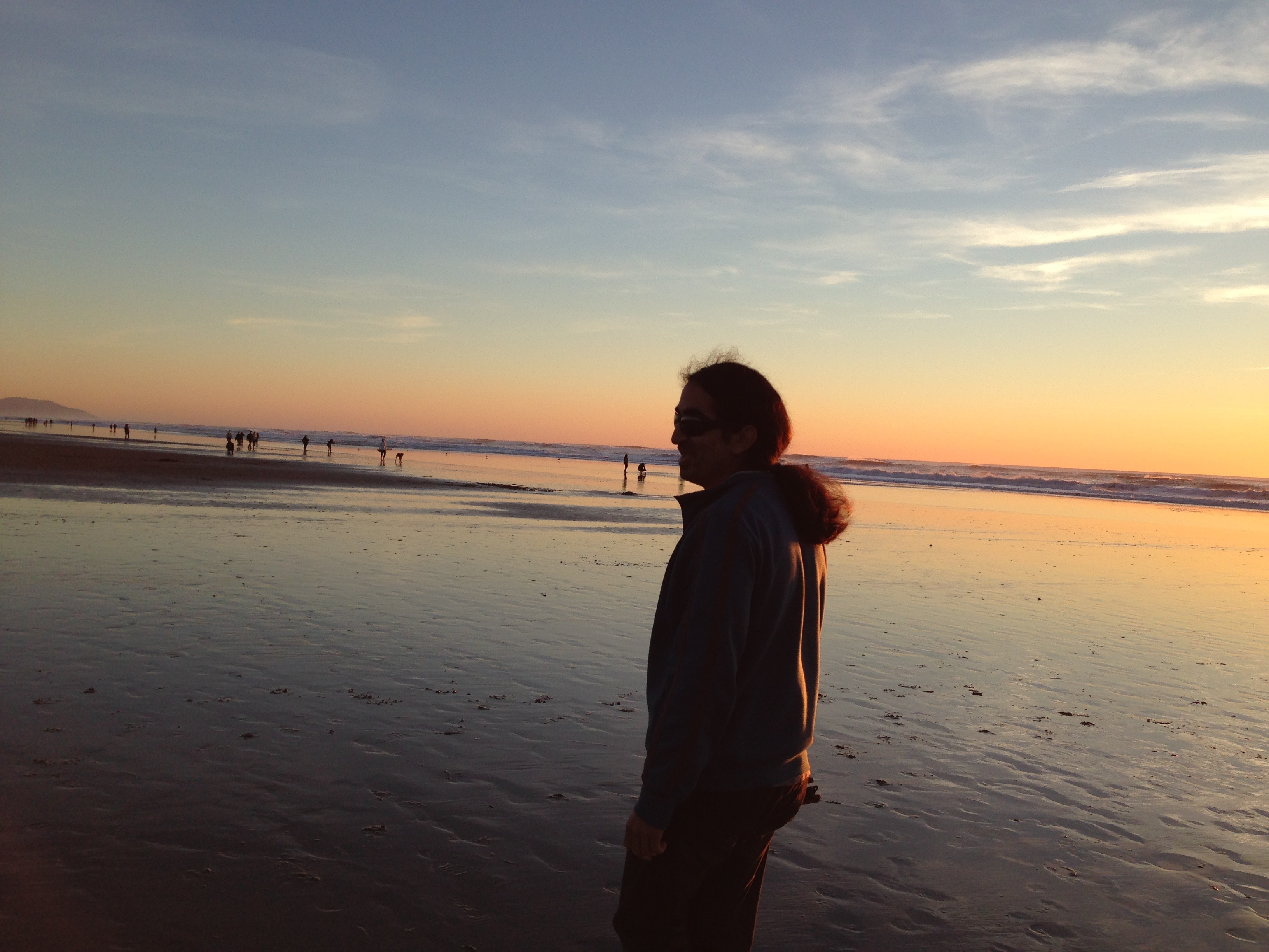 Ahmet is standing on the beach with sunset in the background
